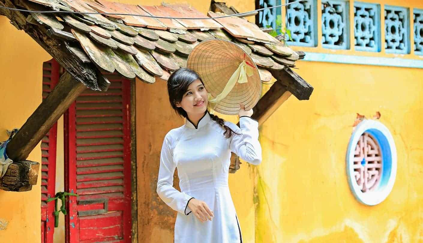 A Vietnamese girl wearing conical hat and long dress ( Ao dai ) is at oldest pagoda in Ho Chi Minh City, Vietnam, Asia