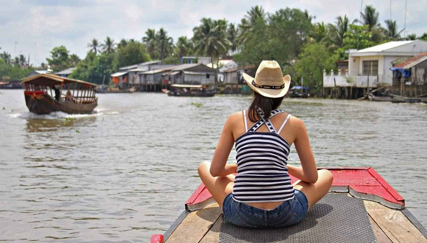 A young woman in a straw hat rides a boat up the Mekong River in Vietnam, Asia