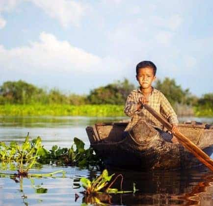 Cambodian boy travelling by boat in his floating village Cambodia